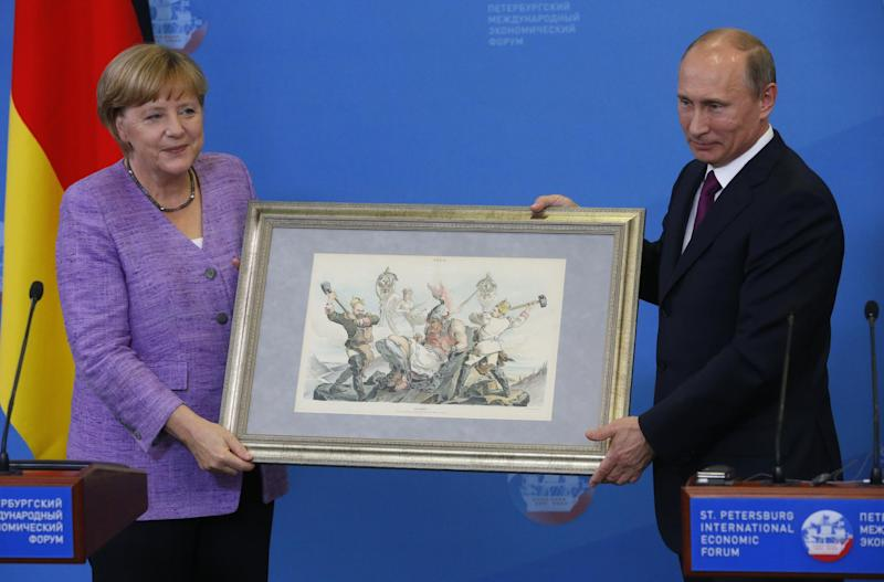 Russian President Vladimir Putin, right, hands German Chancellor Angela Merkel an old lithograph dedicated to the signing of a Russian-German trade agreement in 1894 after a news conference at the economic forum in St.Petersburg, Russia, Friday, June 21, 2013. (AP Photo/Dmitry Lovetsky)