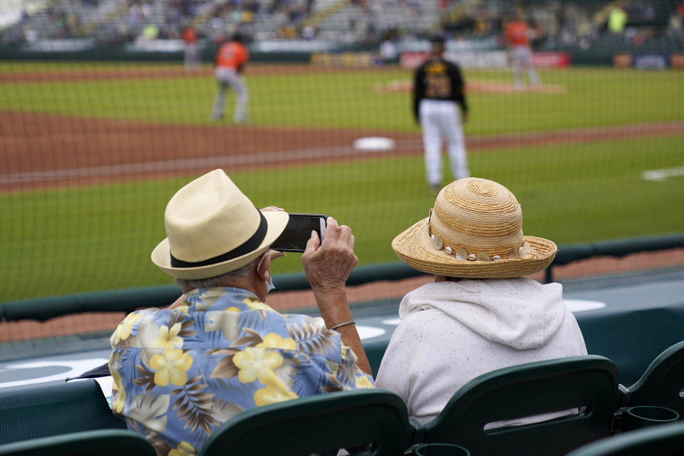 FILE - In this Monday, March 22, 2021 file photo, two older adults socially distanced, watch a spring training exhibition baseball game between the Pittsburgh Pirates and the Baltimore Orioles in Bradenton, Fla. Spring has arrived with sunshine and warmer temperatures, and many vaccinated seniors are emerging from COVID-19-imposed hibernation. (AP Photo/Gene J. Puskar, File)