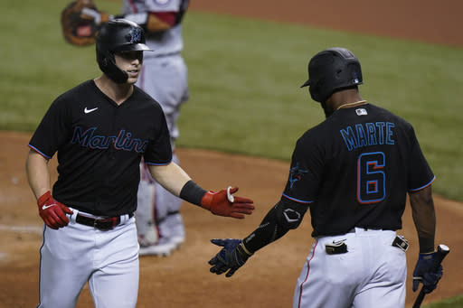 Miami Marlins' Corey Dickerson, left, is congratulated by Starling Marte after hitting a home run during the first inning of the second game of a baseball doubleheader against the Washington Nationals, Friday, Sept. 18, 2020, in Miami. (AP Photo/Wilfredo Lee)