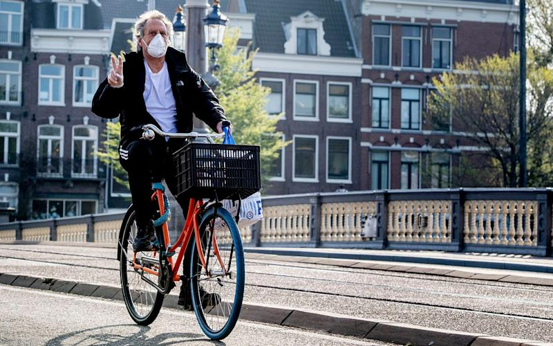 A Dutch cyclist wears a face mask to protect himself from coronavirus. Infections have risen in the Netherlands - SOPA Images