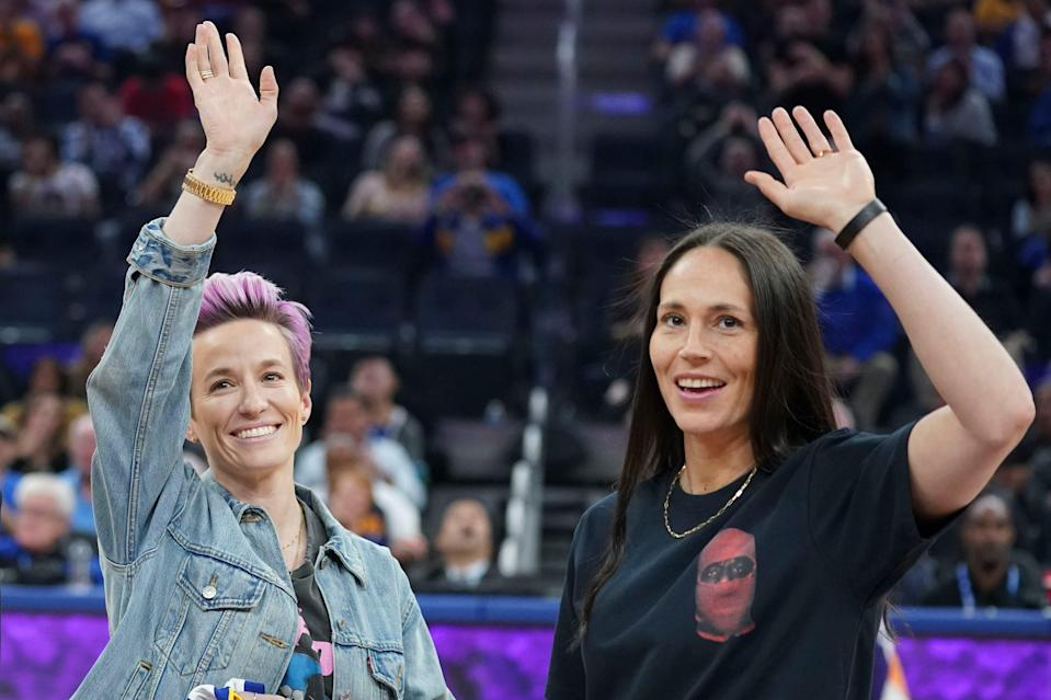 Sue Bird, right, and Megan Rapinoe wave to the crown during a 2019 NBA game between the Golden State Warriors and Phoenix Suns.