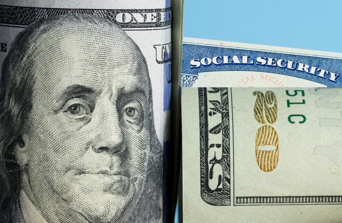 A folded hundred-dollar bill and twenty-dollar bill partially blocking a Social Security card in the background.