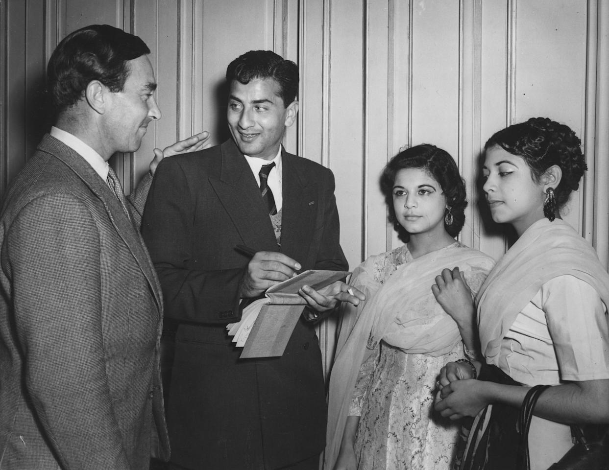 18th August 1954:  Pakistani bowler Fazal Mahmood signs autographs for Najma and Salma Husain, the daughters of Pakistan's Ambassador to Rome, as England cricketer Denis Compton pats him on the back, during a reception for the Pakistan cricket team at the Pakistan High Commissioner's Office in London to celebrate their victory against England in the final Test match at the Oval.  (Photo by Keystone/Getty Images)