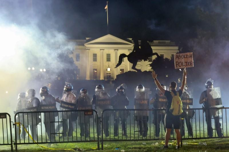 Police in riot gear keep protesters at bay in Lafayette Park near the White House in Washington.