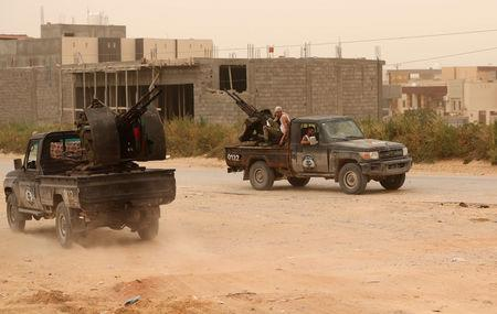 Members of the the Libyan internationally recognised government forces take position during the fighting with the Eastern forces in Ain Zara, in Tripoli