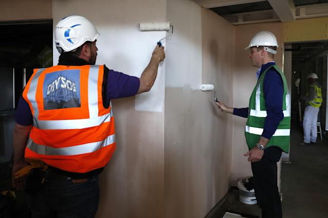 The Duke of Cambridge paints a wall with Nick Knowles in the new gym. (PA)