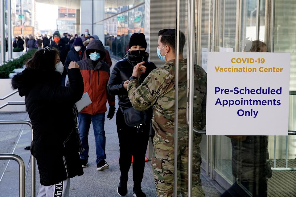 There are financial and psychological costs to getting a COVID-19 vaccine that employers can make easier — or harder — for their workers. Above, people wait to enter the Javits Center in New York City to receive a vaccine in March. (Photo: VIEW press via Getty Images)