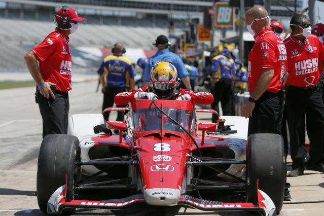 Charlie Kimball climbs into the cockpit of his vehicle during practice for the IndyCar auto race at Texas Motor Speedway in Fort Worth, Texas, Saturday, June 6, 2020. The vehicles new windshield design can be seen beneath Kimball's arms. (AP Photo/Tony Gutierrez)