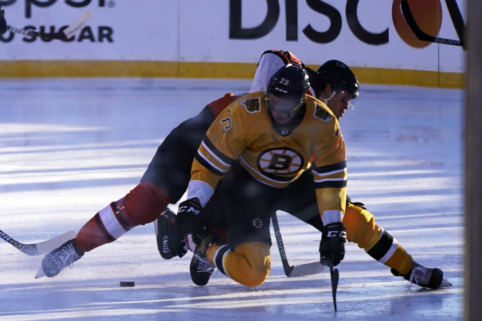 Philadelphia Flyers left wing Joel Farabee, left and Boston Bruins defenseman Charlie McAvoy, right, collide while going for the puck during the first period of an NHL hockey game in Stateline, Nev., Sunday, Feb. 21, 2021. (AP Photo/Rich Pedroncelli)
