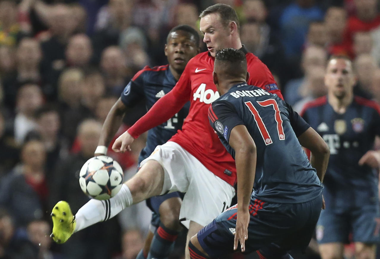 Manchester United's Wayne Rooney is challenged by Bayern's Jerome Boateng, front, and David Alaba during the Champions League quarterfinal first leg soccer match between Manchester United and Bayern Munich at Old Trafford Stadium, Manchester, England, Tuesday, April 1, 2014.(AP Photo/Jon Super)