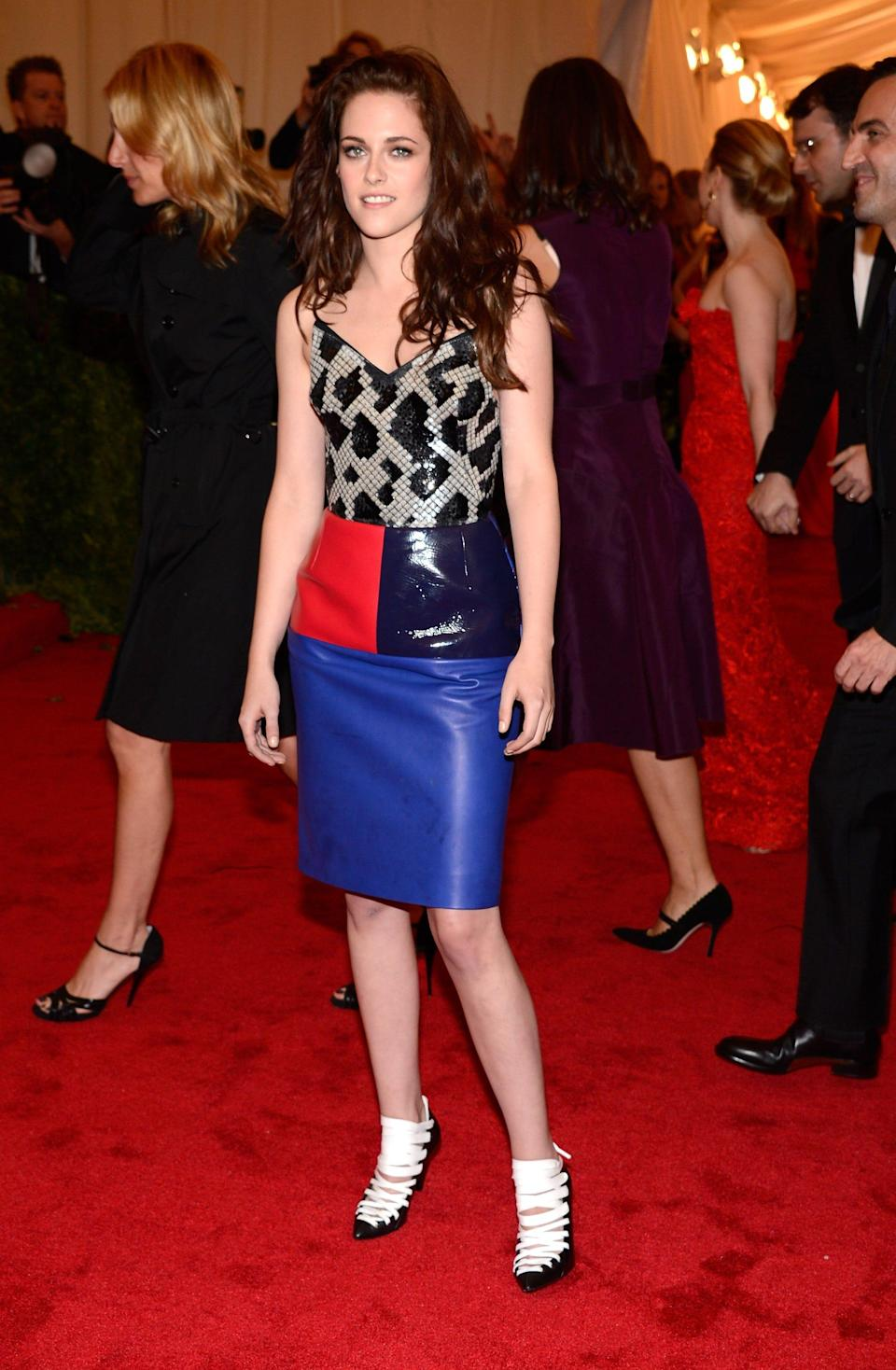 Kristen Stewart stands on a red carpet in an animal print top, color block skirt, and white shoes.