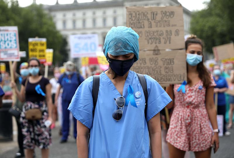 NHS (National Health Service) workers hold a minute's silence to pay tribute to NHS staff who have died with coronavirus during a march through the streets of London on August 8, 2020, to demand a pay rise. (Photo by ISABEL INFANTES / AFP) (Photo by ISABEL INFANTES/AFP via Getty Images)
