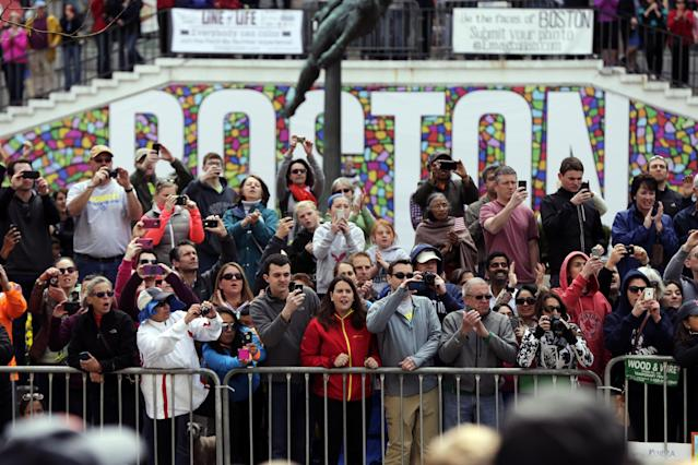 Race fans photograph and cheer for runners competing in the 118th Boston Marathon, Monday, April 21, 2014, in Boston. (AP Photo/Robert F. Bukaty)