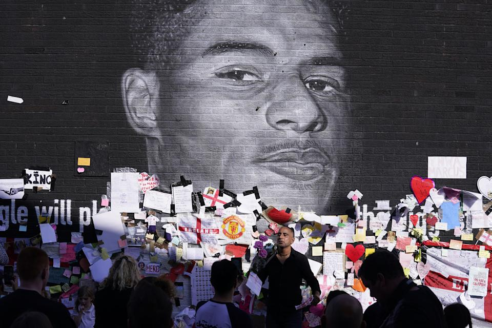 People gather to view the messages of support at the mural of Manchester United striker and England player Marcus Rashford on the wall of the Coffee House Cafe on Copson Street, Withington. The mural appeared vandalised on Monday after the England football team lost the UEFA Euro 2021 final. Picture date: Tuesday July 13, 2021.