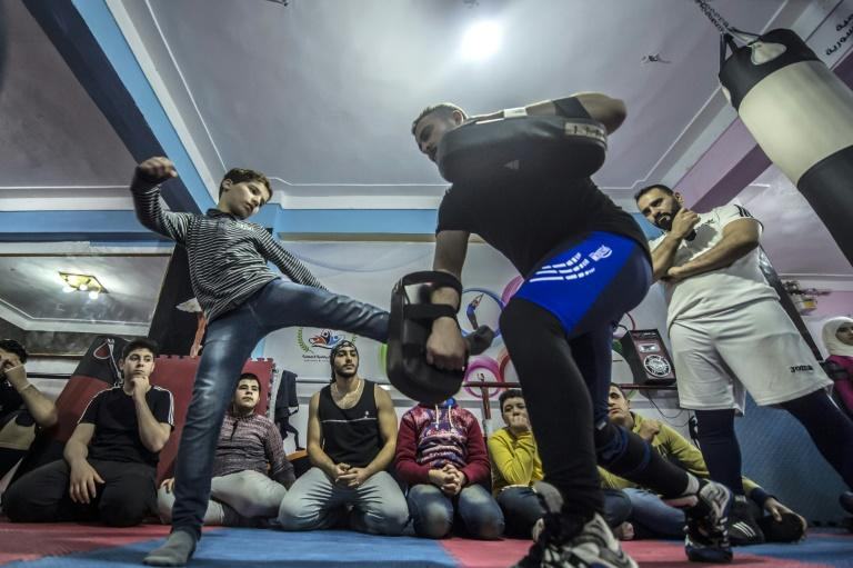 Syrian refugee Amir al-Awad watches as Adel Bezmawy teaches martial arts to youths at a sports academy in Egypt's second city of Alexandria on January 4, 2018