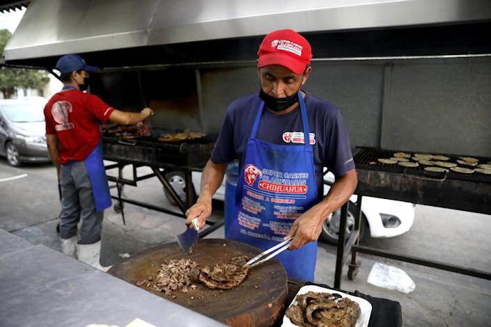 Chefs prepare meat at an outdoor area