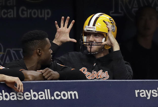 Baltimore Orioles relief pitcher David Hess returns wearing an LSU football helmet after being hit in the eye by a football during pregame. (AP)