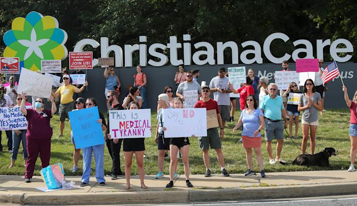 Nearly 400 protesters line the roadway in front of ChristianaCare's Christiana Hospital in a demonstration against the health care system's requirement that employees receive the COVID-19 vaccination.