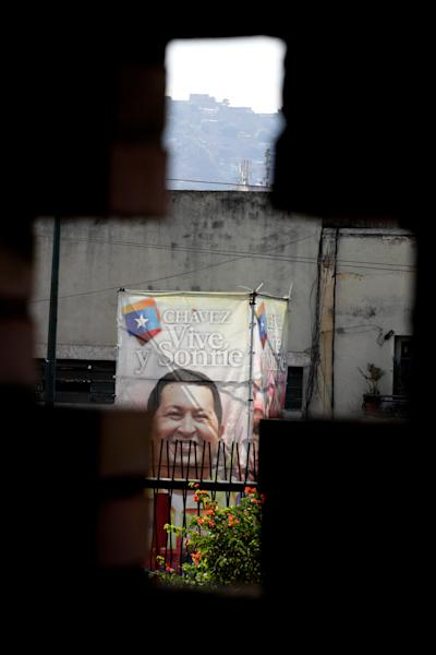 "A poster of Venezuela's President Hugo Chavez is seen through a cross-shaped window, from inside the military hospital's chapel, in Caracas, Venezuela, Tuesday, March 5, 2013. A brief statement read on national television by Communications Minister Ernesto Villegas late Monday carried the sobering news about the charismatic 58-year-old leader's deteriorating health. Villegas said Chavez is suffering from ""a new, severe infection."" The state news agency identified it as respiratory. (AP Photo/Ariana Cubillos)"