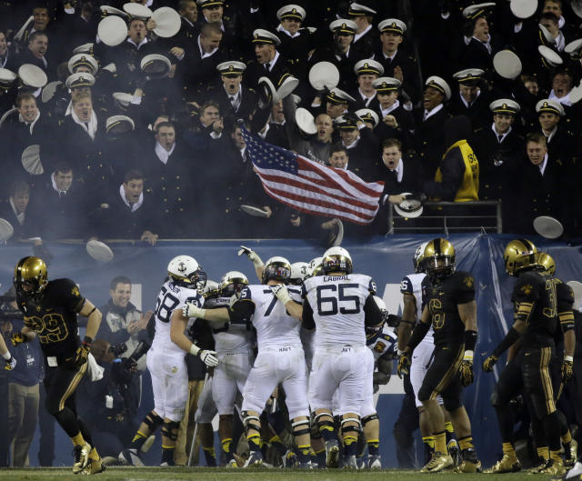 FILE - In this Dec. 8, 2012 file photo, Navy players celebrate after a touchdown during the second half of an NCAA college football game against Army in Philadelphia. The Defense Department says it has temporarily suspended all sports competitions at the service academies as a result of the partial government shutdown. The decision jeopardizes this weekend's football games _ Air Force at Navy and Army at Boston College. (AP Photo/Matt Slocum, File)