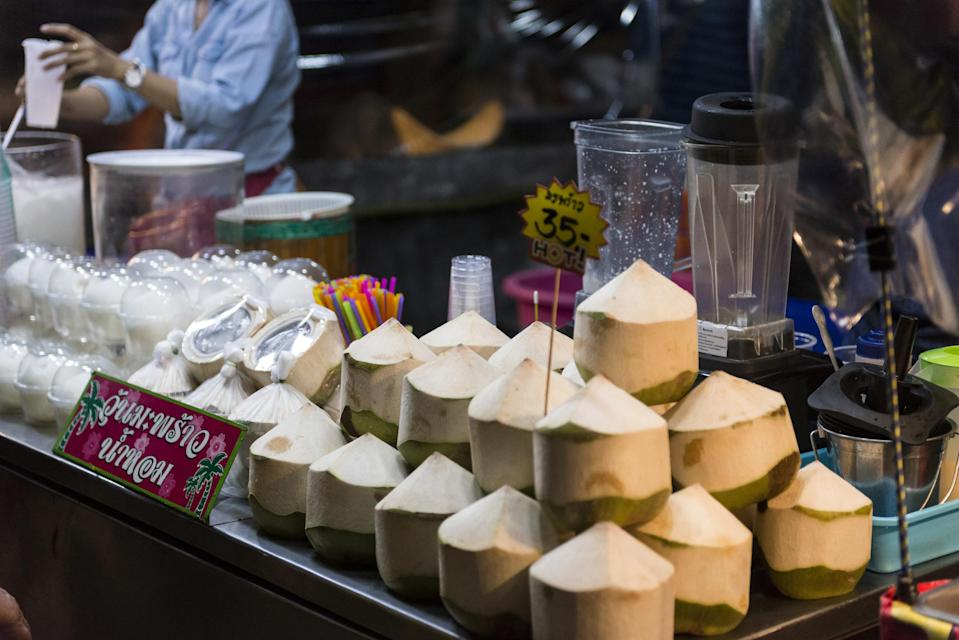 Coconuts and Thai snacks are being sold at a street stall in Tak, Thailand. The coconuts have been sliced so buyers can easily drink from them. The coconuts are a mostly white in color with a bit of green toward the bottom