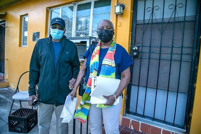 Linda Mallard and her father, John Palmer, stand in front of an apartment in a building they own in the Little River neighborhood of Miami on Jan. 19, 2021. They hired an eviction company to boot out the tenant living at that apartment, who stopped paying rent in February 2020.