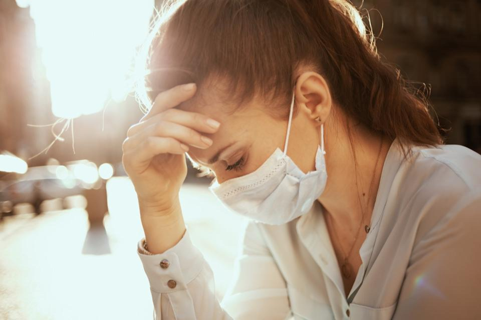 Life during covid-19 pandemic. Portrait of stressed stylish woman in blue blouse with medical mask outdoors on the city street.