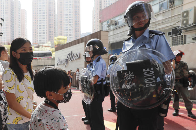 Children wearing masks stand in front of riot police after a fight broke out at the Kowloon Bay district in Hong Kong, Saturday, Sept. 14, 2019. The clashes came after several nights of peaceful rallies that featured mass singing at shopping malls by supporters of the months-long protests demanding democratic reforms. (AP Photo/Kin Cheung)