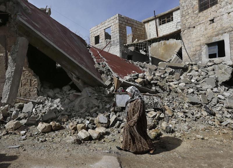 A Syrian woman walks past a house destroyed from a government airstrike,  at Jabal al-Zaweya village of Sarjeh, in Idlib, Syria, Monday Feb. 25, 2013. Syria is ready to hold talks with the armed opposition trying to topple President Bashar Assad, the country's foreign minister said Monday, in the government's most advanced offer yet to try to resolve the 2-year-old civil war through negotiations. (AP Photo/Hussein Malla)