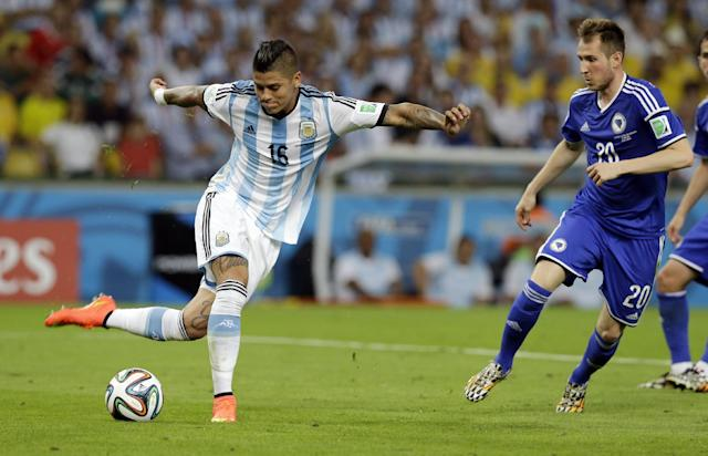 Bosnia's Izet Hajrovic (20) watches as Argentina's Marcos Rojo (16) kicks the ball downfield during their group F World Cup soccer match at the Maracana Stadium in Rio de Janeiro, Brazil, Sunday, June 15, 2014. (AP Photo/Thanassis Stavrakis)