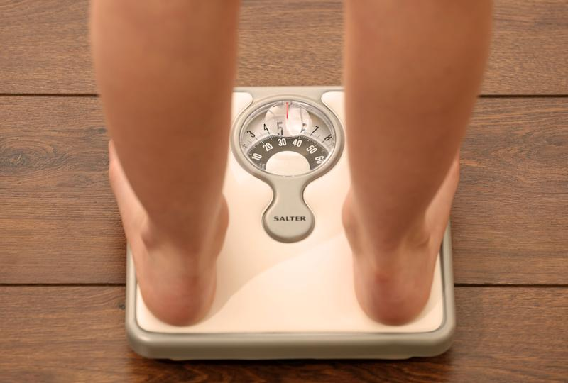 Picture posed by model File photo dated 03/03/14 of an 11 year old girl using a set of weighing scales. Prime Minister Boris Johnson will announce the end of confectionery displays at store checkouts and ban junk food adverts on TV before 9pm as he looks to encourage Britons to shed the pounds.