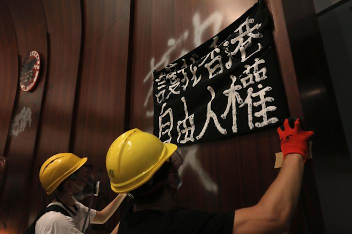 Protesters put up a sign after breaking into the parliament chambers of the government headquarters in Hong Kong on July 1, 2019, on the 22nd anniversary of the city's handover from Britain to China. (Photo: Vivek Prakash/AFP/Getty Images)
