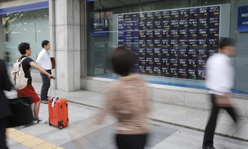 People watch an electronic stock indicator of a securities firm in Tokyo, Tuesday, May 13, 2014. Asian stock markets rose after Wall Street indexes hit record highs, with Japan's Nikkei 225 leading gains as the yen weakened. The Nikkei ended up 275.92 points at 14,425.44 on Tuesday. (AP Photo/Shizuo Kambayashi)