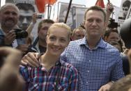 FILE - In this Wednesday, June 12, 2013 file photo, Russian opposition leader Alexei Navalny, right, and his wife, Yulia, left, attend an opposition rally outside the Kremlin in Moscow. Alexei Navalny's energy and charisma propelled him from a lonely role blogging about corruption to widely renown as Russia's leading opposition activist. His projects, including a campaign to run for Moscow mayor, have attracted hordes of volunteers and fundraisers. Now comes a day that looms large for Navalny and the opposition: A court hands down its verdict Thursday in an embezzlement case that could send him to prison for six years. (AP Photo/Alexander Zemlianichenko, File)