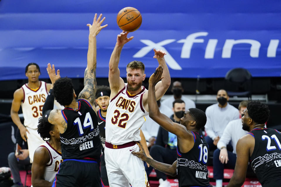 Cleveland Cavaliers' Dean Wade (32) passes the ball between Philadelphia 76ers' Shake Milton (18) and Danny Green (14) during the first half of an NBA basketball game, Saturday, Feb. 27, 2021, in Philadelphia. (AP Photo/Matt Slocum)