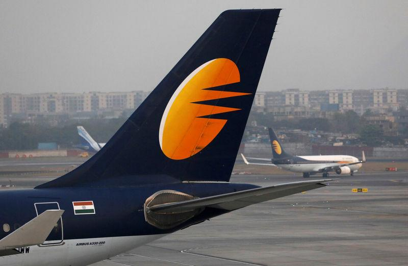 FILE PHOTO: A Jet Airways plane is parked as other moves to runway at the Chhatrapati Shivaji International airport in Mumbai
