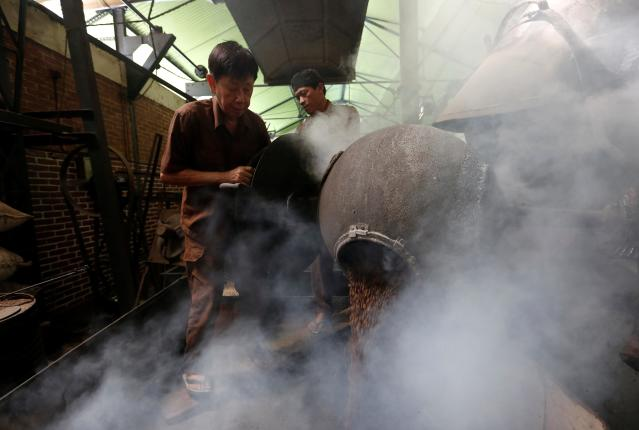 Widya Pratama, the owner of Kopi Aroma, roasts locally grown coffee beans with a traditional wood heated roaster in Bandung, West Java, Indonesia, May 4, 2018. Picture taken May 4, 2018. REUTERS/Willy Kurniawan TPX IMAGES OF THE DAY