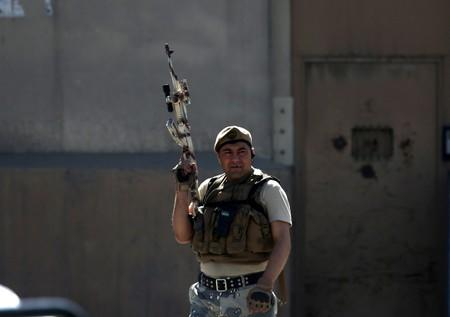 A member of Afghan security force keeps watch at the site of a blast in Kabul