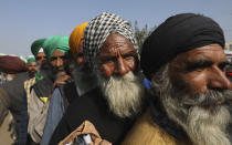 Protesting farmers line up to receive shoes being freely distributed by a voluntary organization during a highway blockade at the Delhi- Haryana border, outskirts of New Delhi, Monday, Dec. 14, 2020. Tens of thousands of farmers have called for a national strike on Monday, the second in a week, to press for the quashing of three new laws on agricultural reform that they say will drive down crop prices and devastate their earnings. (AP Photo/Manish Swarup)