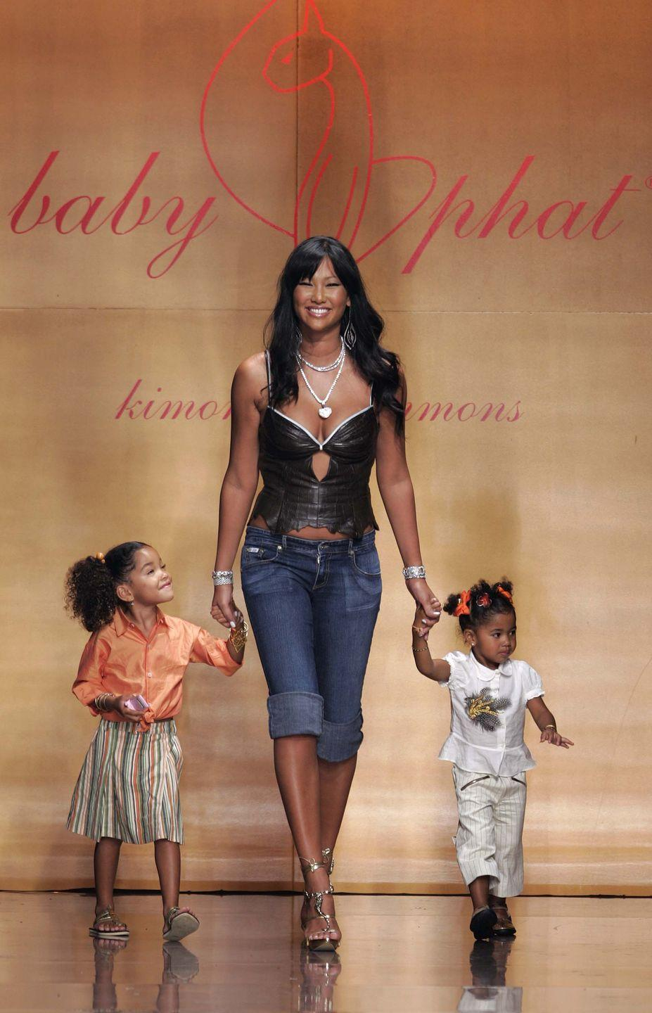 "<p>Kimora Lee Simmons began modeling at the age of 13, walking for some of the biggest names in fashion, and ultimately became a Chanel muse. She married music mogul Russell Simmons, who had his own menswear line, ""Phat Farm."" In 1999, under the ""Phat Fashions"" umbrella, Kimora Lee Simmons created ""Baby Phat"" to give women a much-needed voice in the booming streetwear industry. Baby Phat is a brand that defined fashion in the aughts. The label offered short mini skirts, low rise jeans, slinky crop tops, and of course the bedazzled curvy cat logo inspired by Kimora's cat Max. She democratized fashion with her belief that ""no matter your size or heritage, what united the Baby Phat girl was a desire to look good, feel great, and do it on a dollar."" Simmons became one of the first Black women to run a billion-dollar company. Nearly 10 years after shuttering, Baby Phat is back under the direction of her two teenage daughters.<br> </p>"