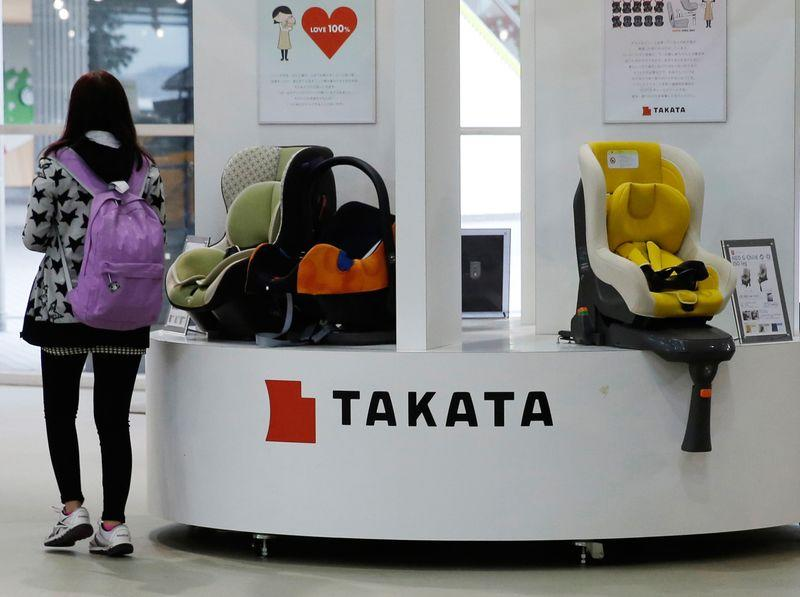 Visitor walks past displays of Takata Corp at a showroom for vehicles in Tokyo in this file photo