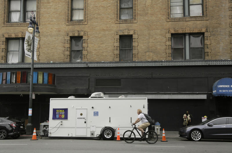 """A man rides his bicycle past a """"Pit Stop"""" public toilet on Sixth Street, Thursday, Aug. 1, 2019, in San Francisco. A 5-year-old portable toilet program in San Francisco that provides homeless people with a private place to go has expanded to 25 locations in the city and has spread to Los Angeles. Not everyone who uses the """"Pit Stop"""" toilets is homeless, but advocates say steam cleaning requests have dropped in surrounding areas. (AP Photo/Eric Risberg)"""