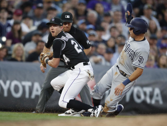 Colorado Rockies third baseman Ryan McMahon, left, forces out San Diego Padres' Ian Kinsler at third base, who was trying to advance on a bunt by Cal Quantrill during the fifth inning of a baseball game Friday, June 14, 2019, in Denver. (AP Photo/David Zalubowski)