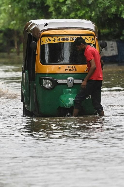 A driver checks his vehicle after it got stuck in water in Faridabad (AFP/Money SHARMA)