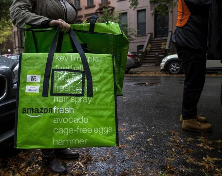 A woman holds an Amazon Fresh delivery bag in Brooklyn, New York