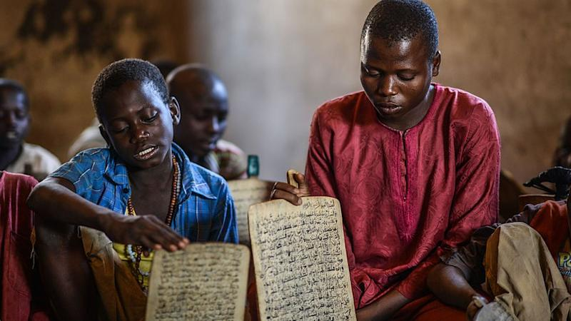 Kids from different district of Nigeria learn to read and memorize the verses of the Quran written with ink on wooden panels at a boarding school in Jimeta, Nigeria on December 08, 2014