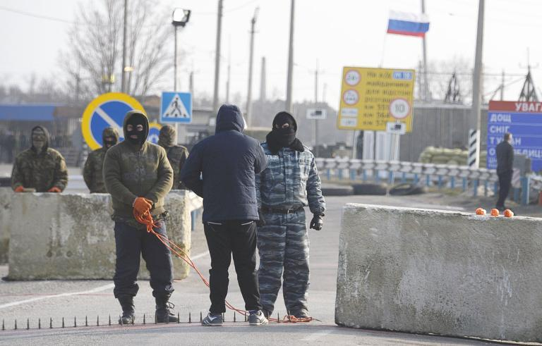 Pro-Russian servicemen in position at the Chongar check point blocking the entrance to Crimea on March 7, 2014. AFP Photo / Alexander Nemenov
