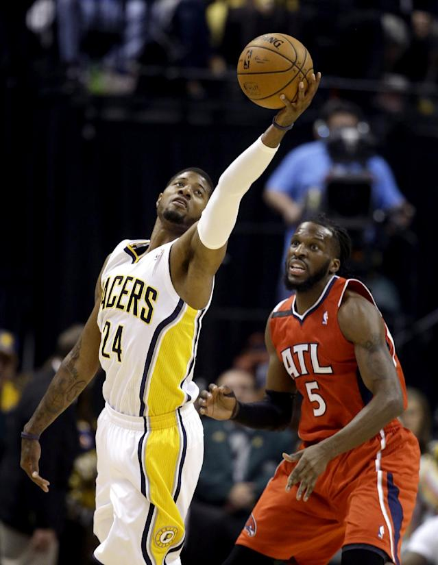 Indiana Pacers' Paul George (24) reaches for the ball as Atlanta Hawks' DeMarre Carroll (5) defends during the first half in Game 5 of an opening-round NBA basketball playoff series Monday, April 28, 2014, in Indianapolis. (AP Photo/Darron Cummings)