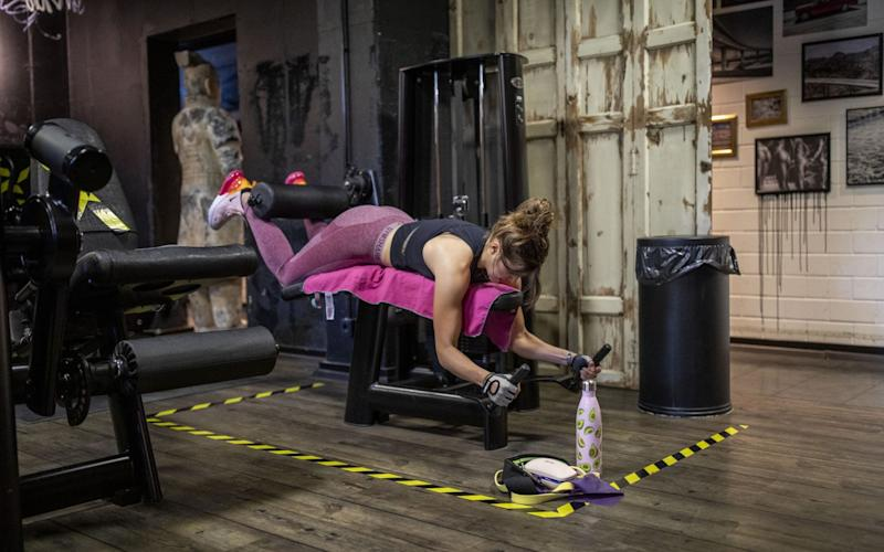 Woman exercises on bench in gym - GETTY IMAGES