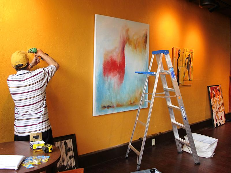 A worker hangs paintings at Table 118, a new restaurant in Lake City, S.C., as part of the ArtFields arts festival on Thursday, April 18, 2013. The 10-day arts festival runs from April 19 through April 28, 2013. Many of the 400 works of art are being displayed in businesses in this old tobacco town. (AP Photo/Bruce Smith)